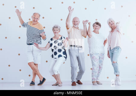 Happy senior people dancing against white background with gold dots - Stock Photo