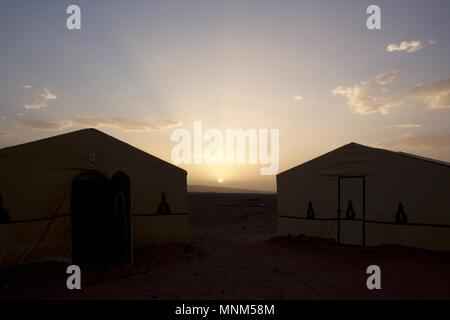 Desert camp tents silhouettes against the sunset in the Zagora desert, Morocco - Stock Photo