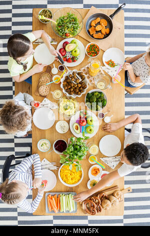 Top view on kids eating healthy dinner at table during birthday party - Stock Photo