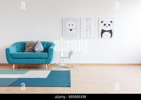 White rocking horse next to blue sofa with pillows in bright kid's room with carpet and gallery of drawings - Stock Photo
