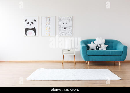 White cushions on aquamarine sofa next to cabinet and rug in kid's room with posters - Stock Photo