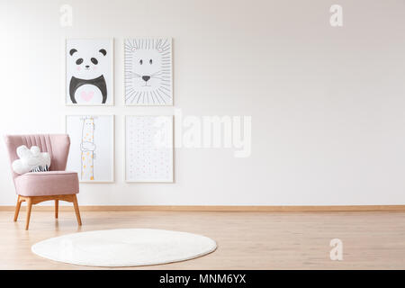 Pink armchair with pillow and white round rug in baby's room with posters on a wall with copy space - Stock Photo