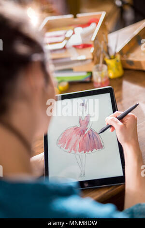Fashion designer drawing a new model on a digital tablet - Stock Photo