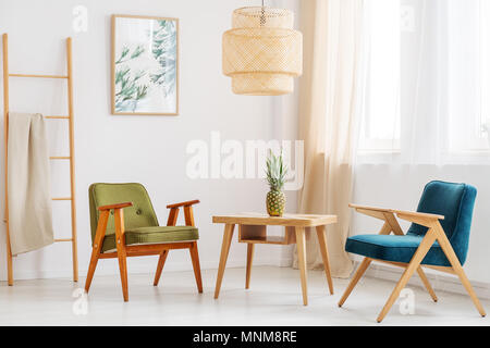 Pineapple on classic table between blue and green chair in simple living room with ladder - Stock Photo