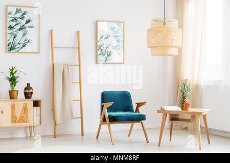 Blue chair in living room with pineapple on wooden table and decorative vase on rustic cupboard - Stock Photo