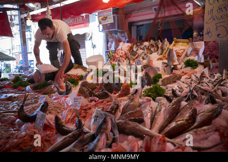 A man sells fresh fish at the Ballaro market in Palermo, Sicily on April 24, 2018. Ballaro is traditional market where you can find regional agricultu - Stock Photo