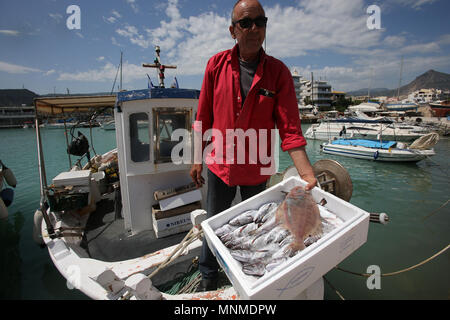Xylokastro, Peloponnese in Greece. 17th May, 2018. A local fisherman prepares to sell his cod and hake to restaurants in the marina of Xylokastro, a popular tourist destination of Peloponnese in Greece, May 17, 2018. Due to the economic crisis and over exploitation of the sea, the majority of Greek fishermen is hard to make a living. Credit: Marios Lolos/Xinhua/Alamy Live News - Stock Photo