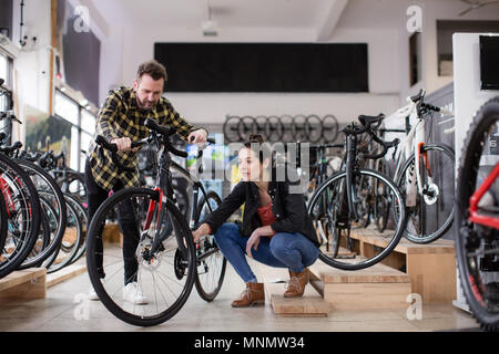 Small business owner helping customer in a bike store - Stock Photo