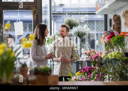 Florist serving customer in a store - Stock Photo