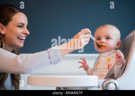 Mother feeding baby (18-23 months) - Stock Photo