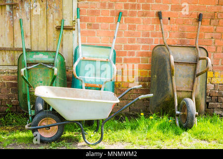 Four garden wheelbarrows, one on the grass and three leaning against a brick wall - Stock Photo