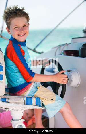 Cute little boy at sail boat wheel - Stock Photo