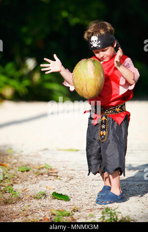 Boy dressed in pirate costume throwing coconut - Stock Photo