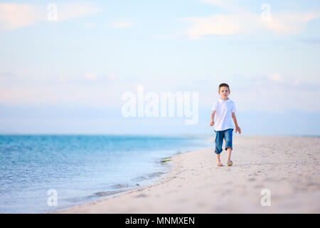 Little boy walking along tropical beach - Stock Photo