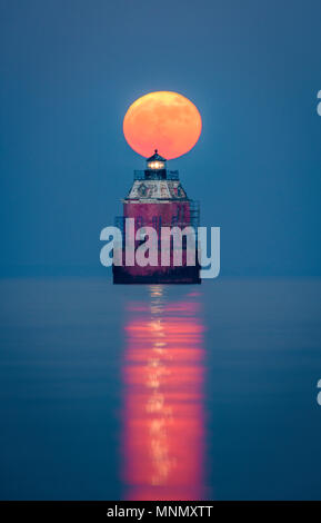 A full, super moon rises behind the Sandy Point Lighthouse, on the Chesapeake Bay, Near Annapolis, Maryland. - Stock Photo
