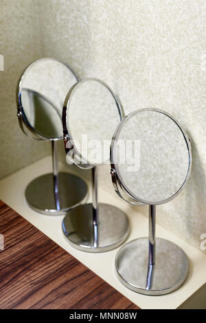 Mirrors for make-up stand on the table near the wall. - Stock Photo