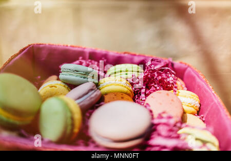 Colorful macaroons and flowers on wooden table. Sweet macarons in gift box. Flat lay - Stock Photo