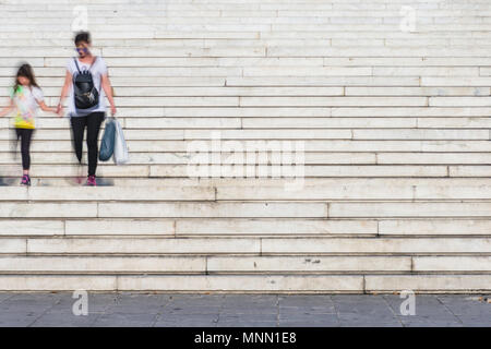 Blurred people walking up and down the steps in central square in Athens, Greece - Stock Photo