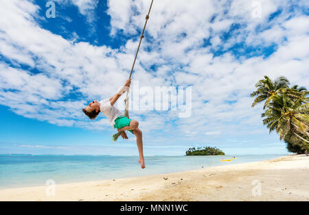 Cute boy having fun swinging on a rope at tropical island beach - Stock Photo
