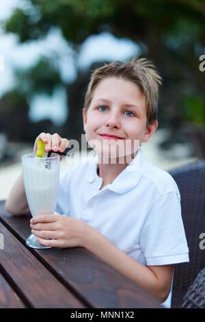 Teenage boy drinking milkshake in outdoor cafe - Stock Photo