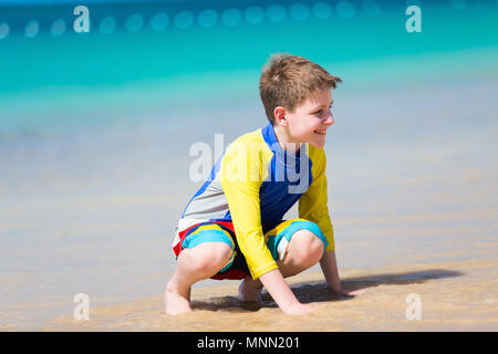 Handsome pre-teen age boy playing with sand at tropical beach on summer vacation - Stock Photo