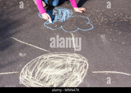 Little child is drawing a landscape onto the sidewalk - Stock Photo
