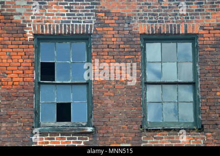 Two broken windows on an old industrialo red brick building in the warehouse district of New Orleans - Stock Photo