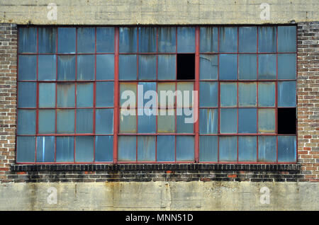 A large window on an old industrial building in the warehouse district of New Orleans - Stock Photo