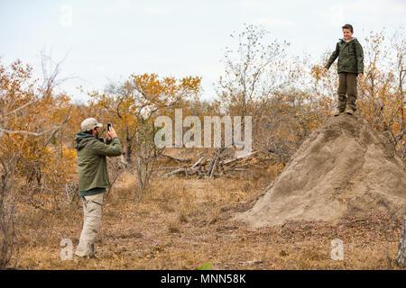 Father taking photo of teenage boy on top of high termite mount in Samburu national park,  Kenya. - Stock Photo