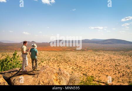 Family of father and child on African safari vacation enjoying view over Samburu Kenya - Stock Photo