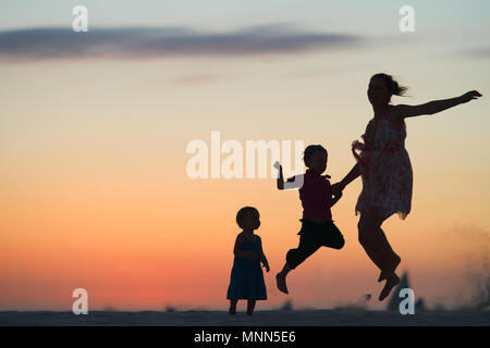 Mother and two kids silhouettes jumping on beach at sunset - Stock Photo