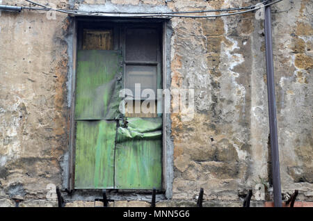 A window on an old building in Palermo, Sicily, that's been boarded up and covered with green metal - Stock Photo