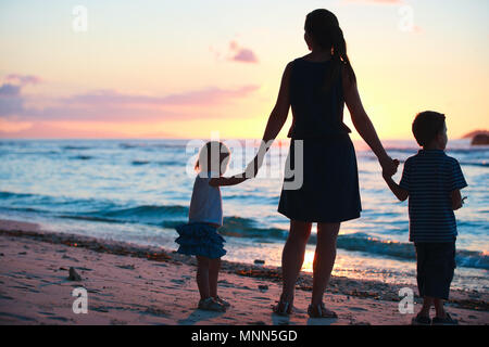 Mother and two kids silhouettes on beach at sunset - Stock Photo