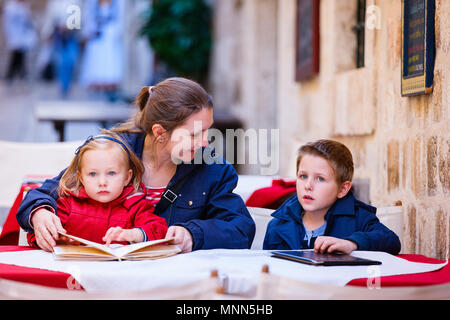 Young mother and her two kids at outdoor cafe on autumn or spring day - Stock Photo
