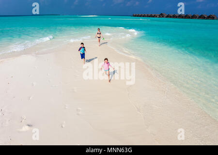 Above view of kids in a colorful sun protection swimwear running and having fun at beach - Stock Photo