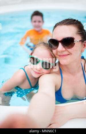 Happy mother and her kids at outdoors swimming pool taking selfie on tropical vacation - Stock Photo