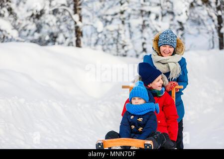 Beautiful family of mother and kids enjoying snowy winter day outdoors having fun sledging - Stock Photo