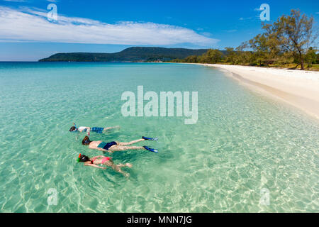Above view of  mother and kids snorkeling in a clear tropical water near exotic white sand beach - Stock Photo