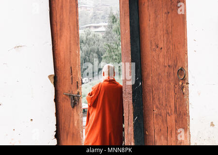 A Buddhist monk standing by a door of Changangkha Lhakhang, Bhutan - Stock Photo