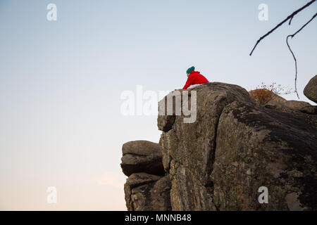 Young man doing parkour standing on rock and looking at landscape in sunset lights. - Stock Photo