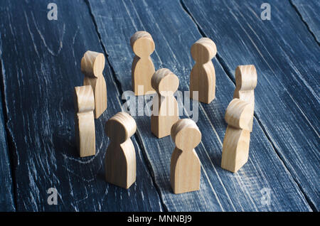 Wooden curly people stand in a circle around the person on a dark background. The concept of communication, teamwork, hierarchy and authoritarianism.  - Stock Photo