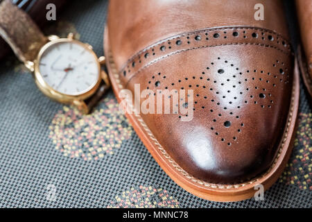 Men's leather new brown shoes closeup still life on couch with belt, getting ready wedding groom or interview preparation macro of vintage retro luxur - Stock Photo