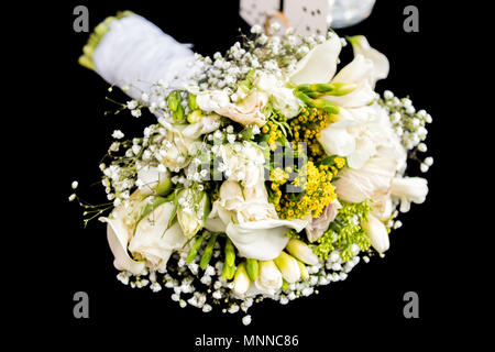 Wedding bouquet with many flowers, green yellow lily isolated lying on black table background macro closeup floral arrangement - Stock Photo