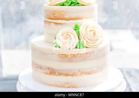 Macro closeup of three tiered vanilla golden light white yellow cream sponge wedding cake with rose flowers decoration on bright stand, green leaves - Stock Photo