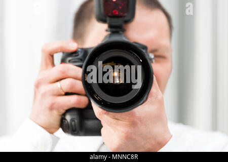 One young wedding photographer, ring, in dress shirt standing with camera, external flash, taking pictures macro closeup of lens, reflection - Stock Photo