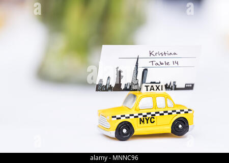 New York City, USA - April 7, 2018: NY NYC yellow taxi cab souvenir cute small toy car wedding favor gift decorations on reception table white cloth c - Stock Photo