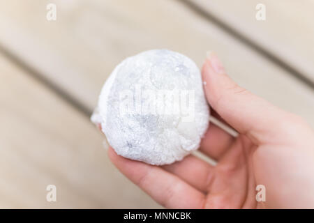 Hand holding round whole piece of mochi sticky glutinous rice cake dessert filled with red bean adzuki jam filling - Stock Photo
