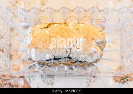 Closeup of golden baked whole poppy seed roll cake, or chocolate babka pastry bread in crystal glass dish on table for festive traditional holiday - Stock Photo