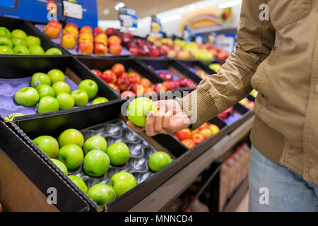 Many varieties assorted apples on display shelf in grocery store boxes in aisle, supermarket inside, man person customer holding granny smith green fr - Stock Photo
