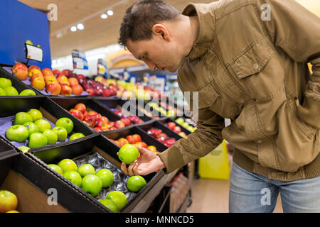 Many varieties assorted apples on display shelf in grocery store boxes in aisle, supermarket inside, man person customer holding choosing granny smith - Stock Photo